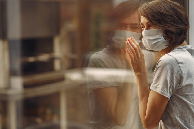 mujer-mascara-junto-ventana_1157-31619